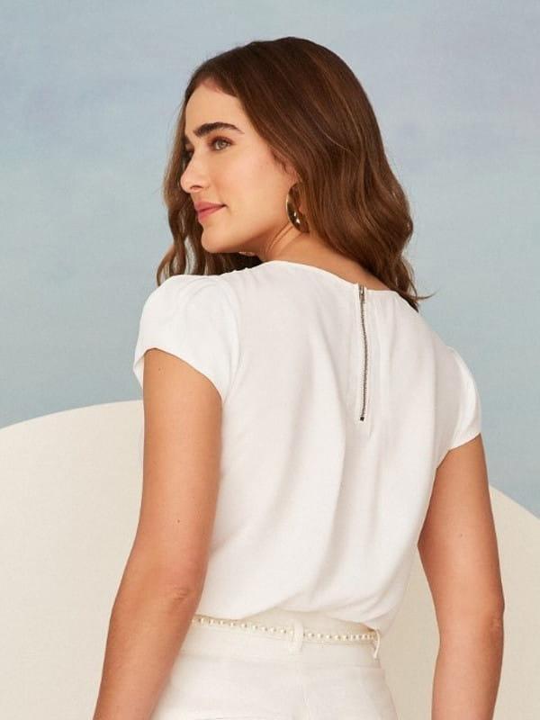 Blusas femininas para uniforme: modelo vestindo uma blusa de crepe com detalhe gota na cor branca - costas.