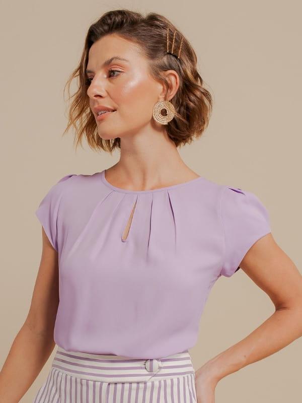 Blusas femininas para uniforme: modelo vestindo uma blusa de crepe com detalhe gota na cor lilás.