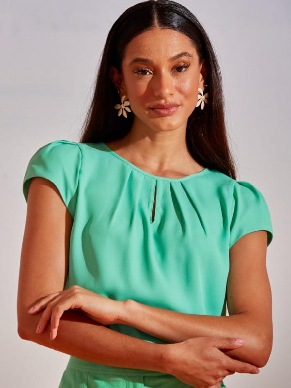 Blusas femininas para uniforme: modelo vestindo uma blusa de crepe com detalhe gota na cor verde claro.