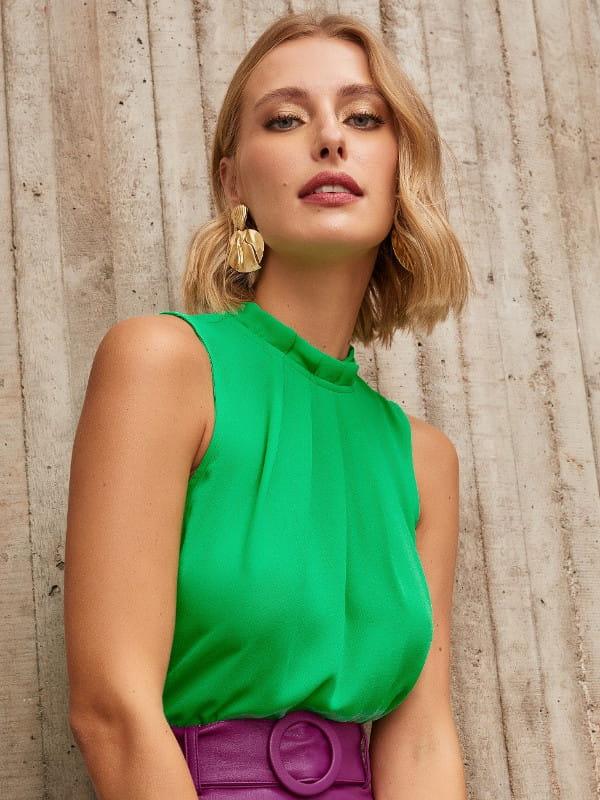 Blusas femininas para uniforme: modelo vestindo uma regata de crepe com pregas na gola verde aceso.