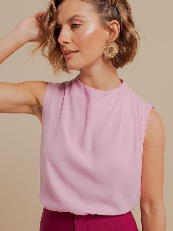 Blusas femininas para uniforme: modelo vestindo uma regata de crepe com pregas no ombro rosa claro.