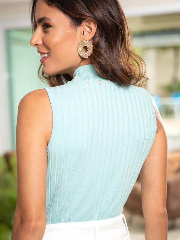 Blusa canelada gola alta: modelo mostrando as costas de uma regata verde clara.