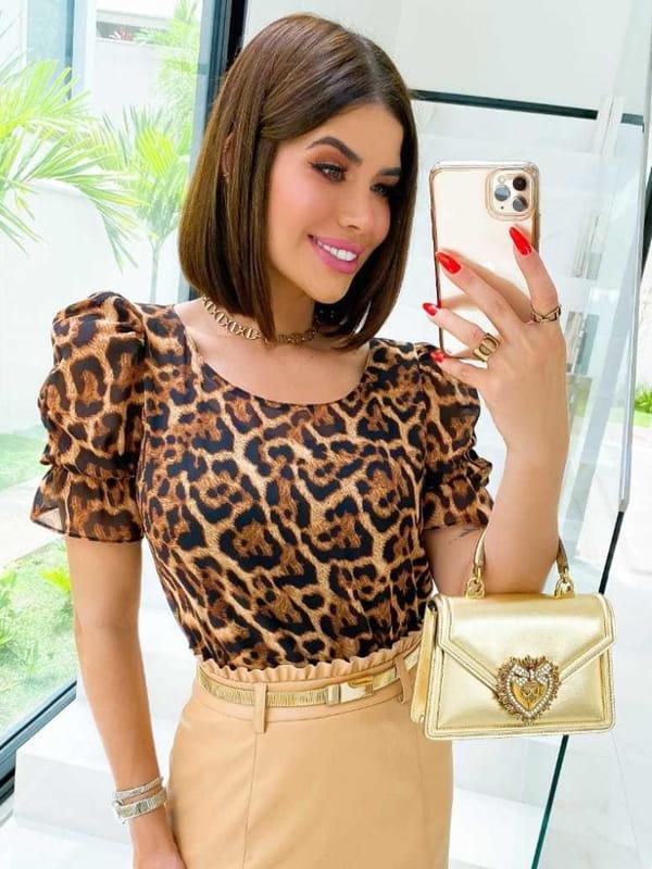 Blusa de oncinha: modelo vestindo uma blusa animal print de oncinha com mangas bufantes.