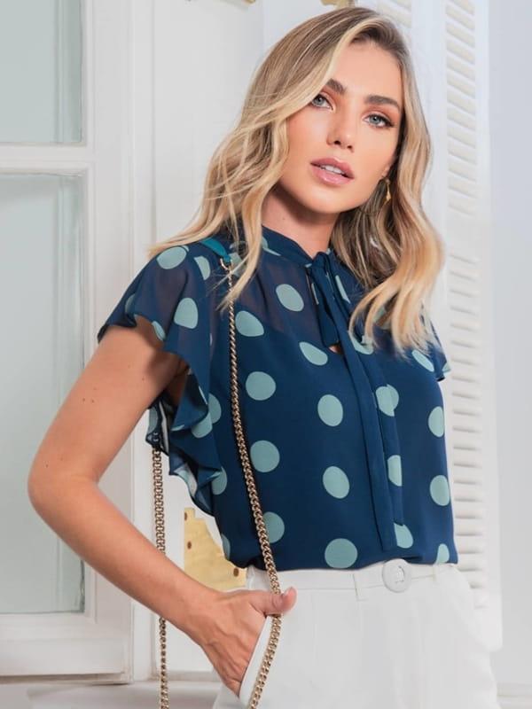 Blusa feminina social: modelo vestindo uma blusa de crepe chiffon com estampa maxi poás.
