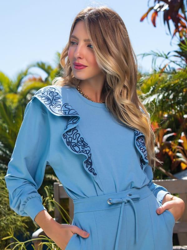 Blusa moletinho feminino: modelo vestindo um moletinho azul com babado.