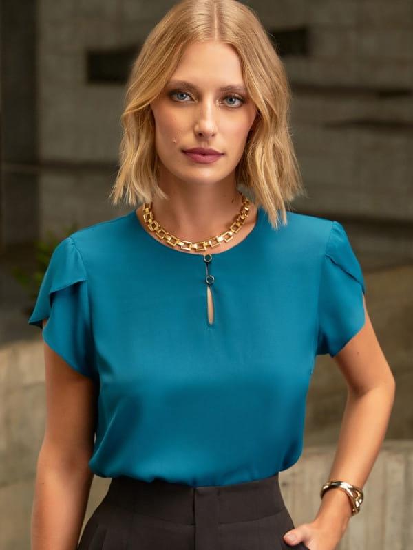 Blusa social feminina: modelo vestindo uma blusa azul petróleo com botões no decote.