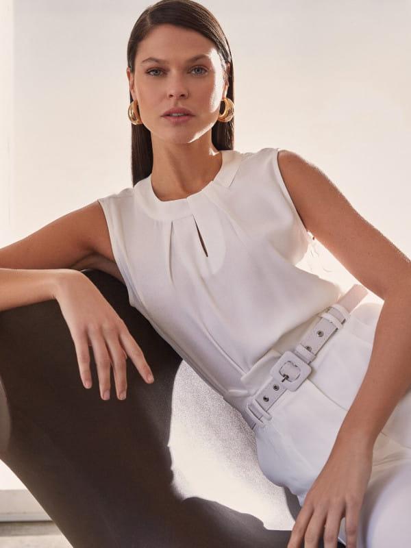 Blusa social feminina: modelo vestindo uma blusa social branca alfaiataria com pregas.