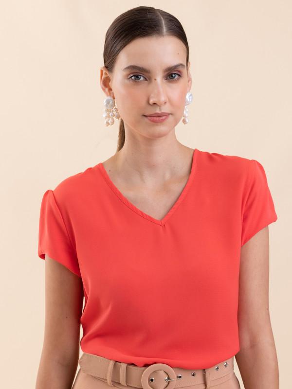 Blusas femininas 2020: modelo vestindo uma blusa de crepe decote V tangerina.