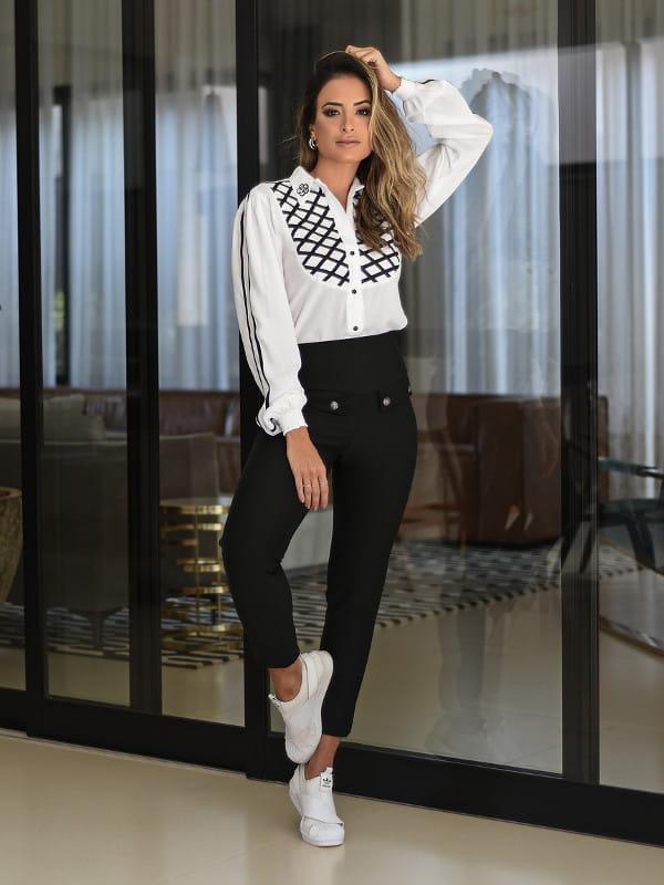 Modelo vestindo uma blusa feminina de crepe viscose branca com detalhe preto.