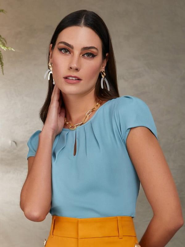 Blusas femininas 2021: modelo vestindo uma blusa de crepe com detalhe gota azul claro.