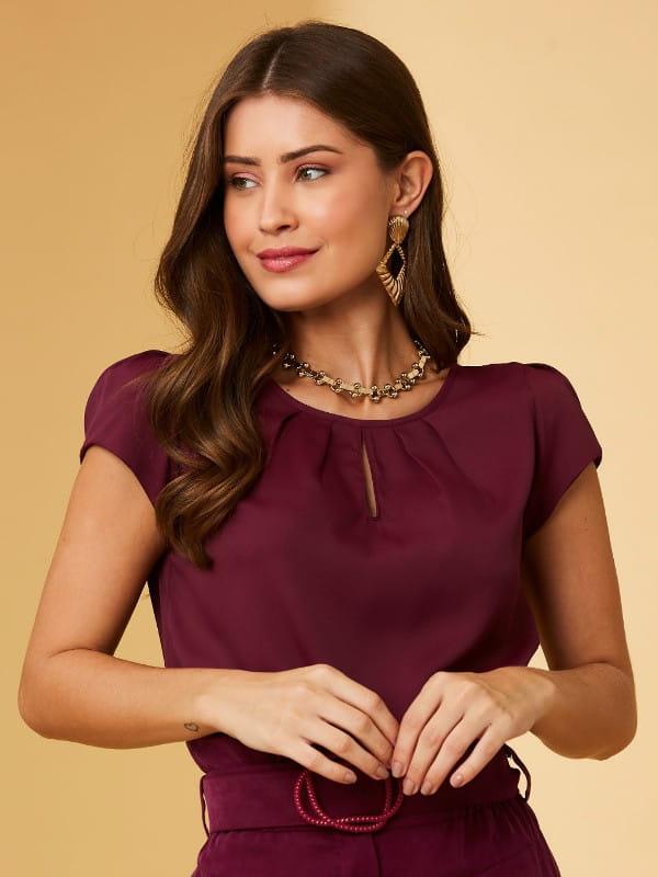 Blusas femininas 2021: modelo com uma blusa de crepe detalhe gota cor ameixa.