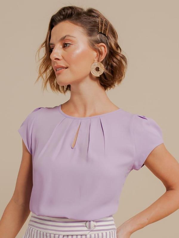 Blusas sociais femininas modernas: modelo vestindo uma blusa com detalhe gota na cor lilás.