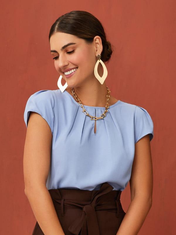 Modelos de blusas femininas: modelo vestindo uma blusa de crepe gota azul claro.