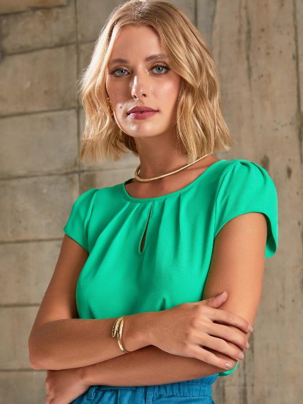 Blusas femininas 2021: modelo vestindo uma blusa de crepe com detalhe gota na cor verde aceso.