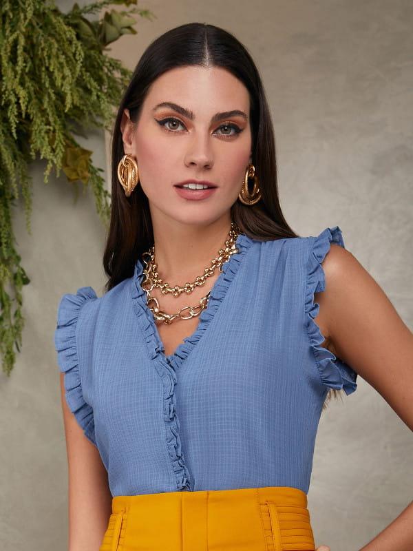 Blusas femininas para trabalhar: modelo vestindo uma regata com manga cavada e babadinhos.