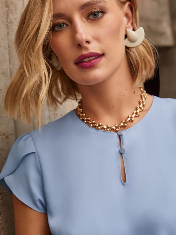 Blusas para trabalhar: modelo vestindo uma blusa de crepe com botões e decote gota azul clara.