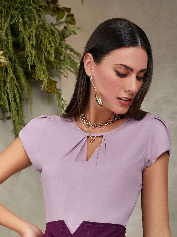 Blusas femininas para trabalhar: modelo vestindo uma blusa de crepe lilás com decote triângulo e pregas.