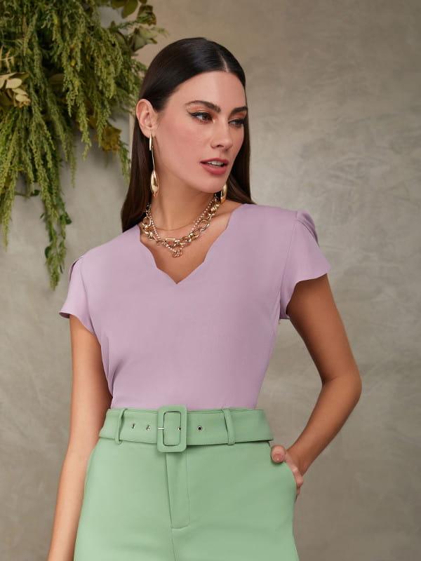 Blusas femininas para trabalhar: modelo vestindo uma blusa de crepe lilás com decote nuvem.