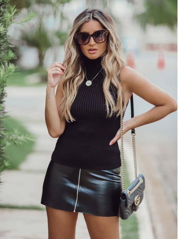 Blusas femininas para trabalhar: modelo vestindo uma regata de tricot com golinha alta preta.
