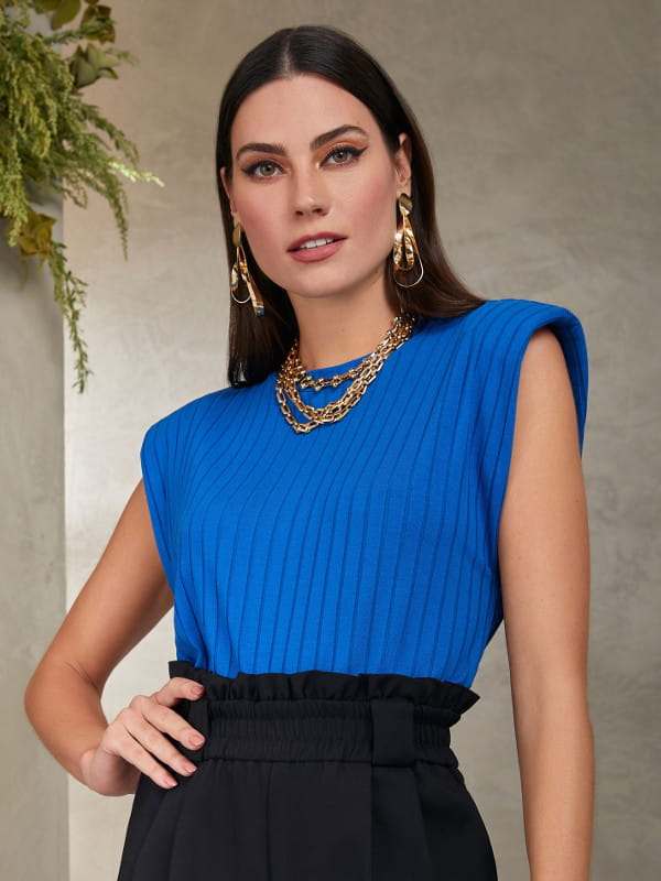 Blusinhas para o verão: modelo vestindo uma blusa azul manga cavada.