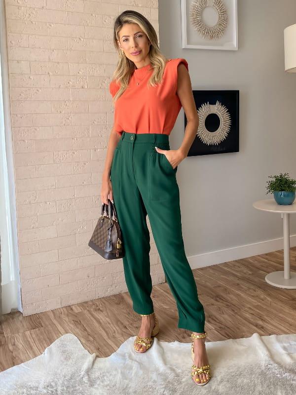 Blusinhas para o verão: modelo vestindo um look com blusa de manga cavada e calça jogger.