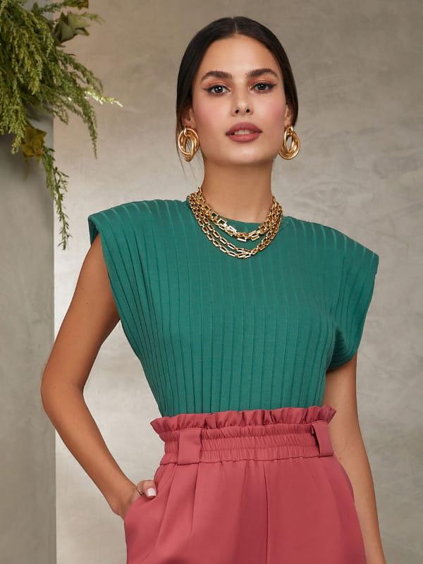 Blusinhas para o verão: modelo vestindo uma blusa verde manga cavada.