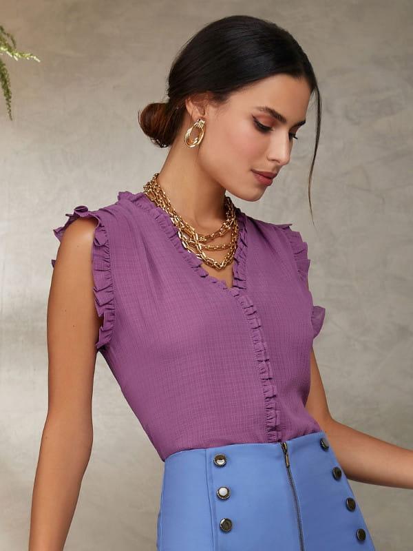 Blusinhas para o verão: modelo vestindo uma blusa com manga cavada com babadinhos discretos cor lilás.