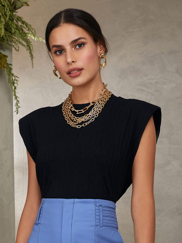 Blusinhas para o verão: modelo vestindo uma blusa preta com ombreira.