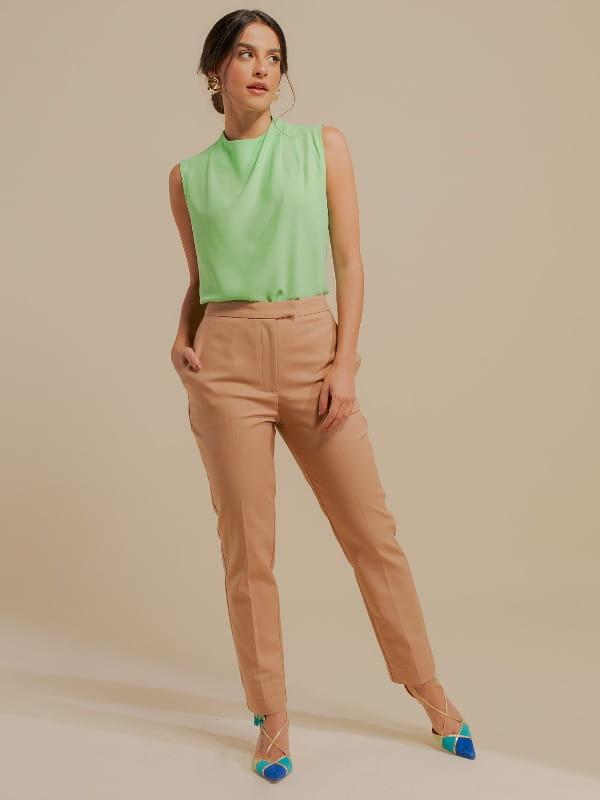 Inspire-se nos novos looks da semana: modelo vestindo uma calça de sarja alfaiataria bege.