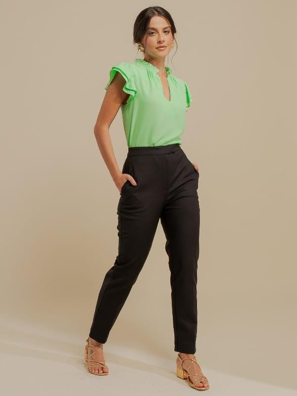 Inspire-se nos novos looks da semana: modelo vestindo uma calça de sarja alfaiataria preta.