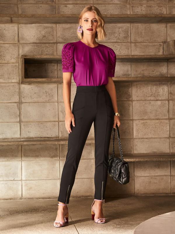 A calça skinny e a sua versatilidade: modelo vestindo uma blusa fucsia e uma calça skinny preta.