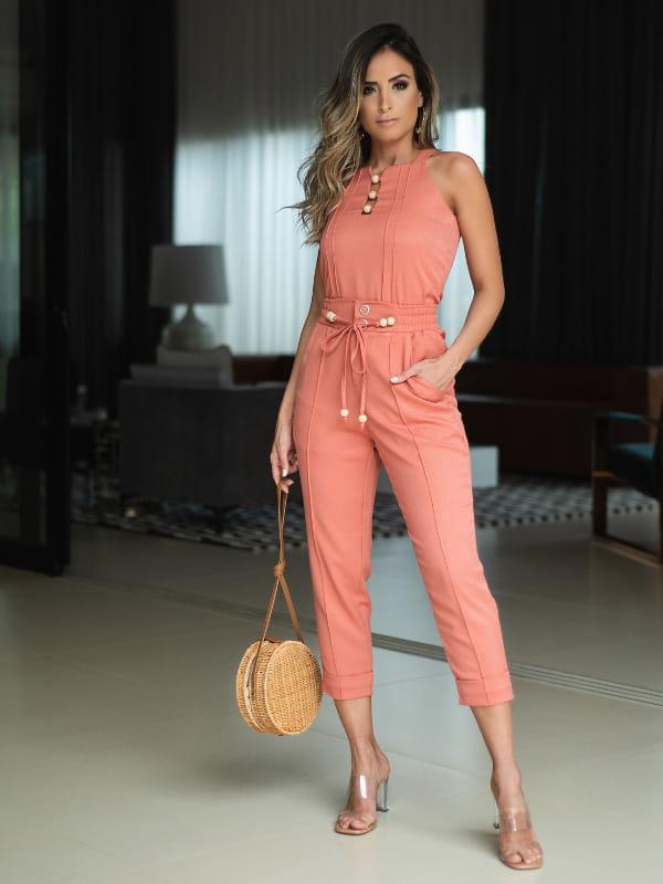 Calça alfaiataria feminina: modelo vestindo uma calça alfaiataria salmão.