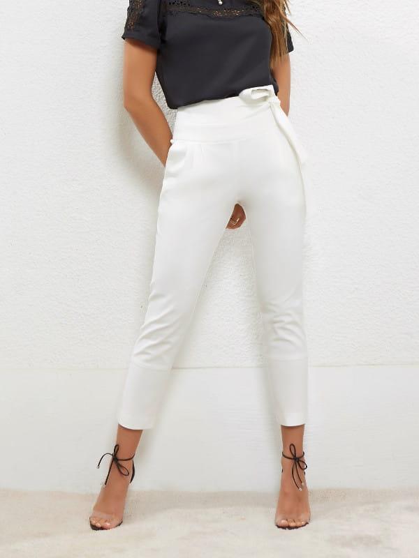 Calça carrot feminina: modelo vestindo uma calça carrot com com amarração branca.