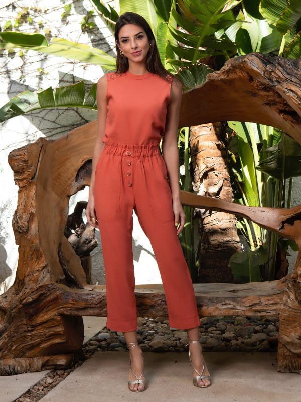 Calça carrot feminina: modelo vestindo uma calça carrot e blusa na cor terracota.