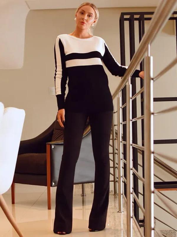 Calça flare feminina: modelo vestindo uma calça flare com blusa de tricot.