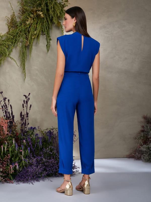 Looks com calça jogger feminina: modelo de costas vestindo calça de crepe azul royal.