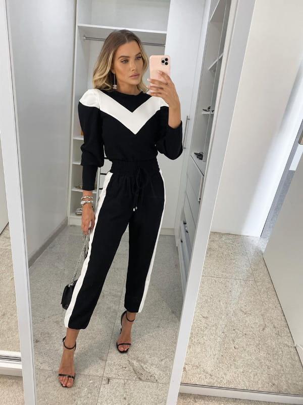 Looks com calça jogger feminina preta: modelo vestindo calça jogger bicolor preta e branca.