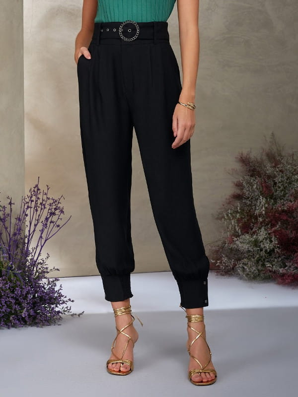 Looks com calça jogger feminina: modelo vestindo calça de crepe preta.
