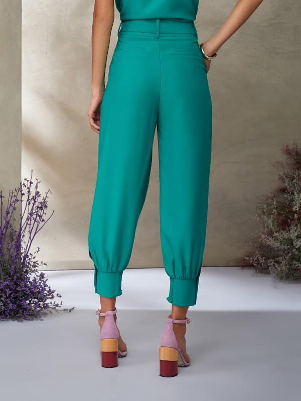 Looks com calça jogger feminina: modelo de costas vestindo calça de crepe e blusa verdes.