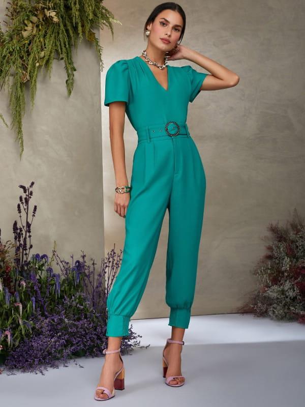 Looks com calça jogger feminina: modelo vestindo calça de crepe e blusa verdes.