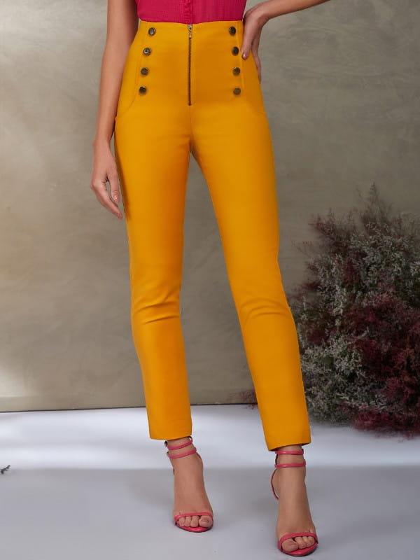 Calça skinny feminina: modelo vestindo uma calça skinny na cor amarela com botões frontais.