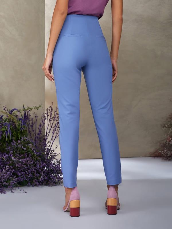 Calça skinny feminina: modelo vestindo uma calça skinny na cor azul com botões frontais.
