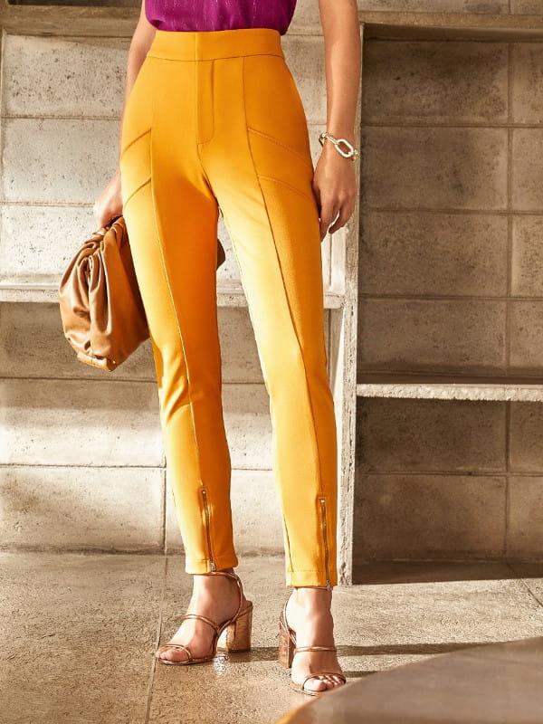 Calça skinny feminina: modelo com uma calça skinny na cor mostarda com zíper na barra.
