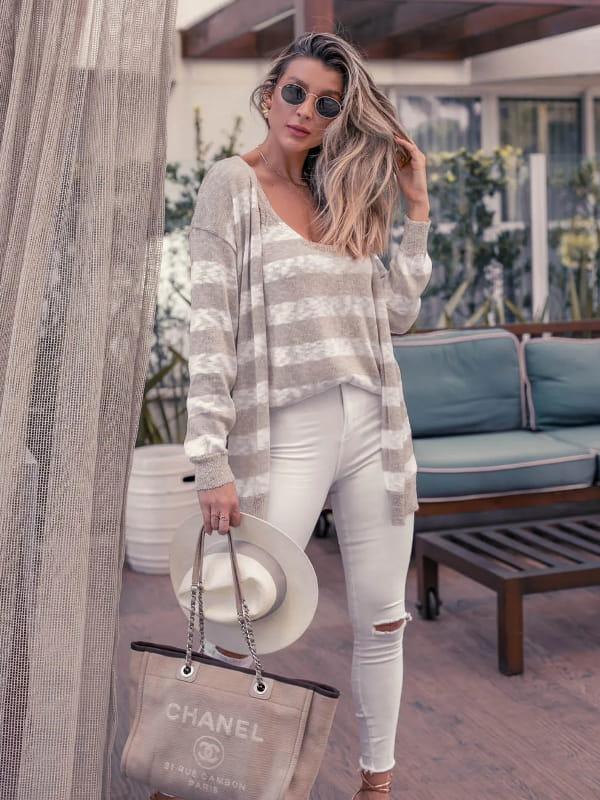 Looks com cardigan feminino longo: modelo vestindo um look com cardigan segurando um chapéu e bolsa.