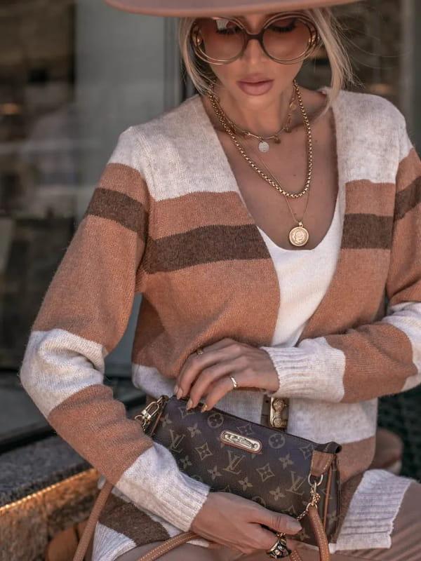 Looks com cardigan feminino longo: modelo mostrando detalhes de um cardigan e bolsa.