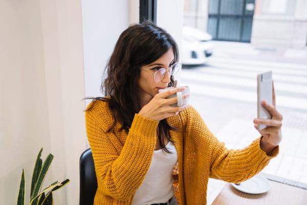 Cardigans femininos: modelo vestindo um cardigan e tomando um café.
