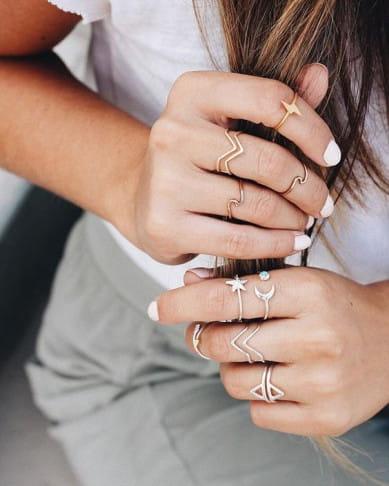Como se vestir com clima instável: modelo usando vários anéis diferentes.