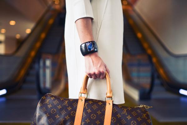Como comprar sua bolsa Louis Vuitton Original e arrasar no look: modelo com um vestido preto e botões em toda a frente.