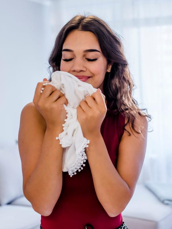 Como lavar blusa de tricot: moça cheirando sua blusa limpinha.