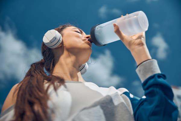 Saiba como se cuidar no inverno: mulher bebendo água em uma garrafa após seu treino.
